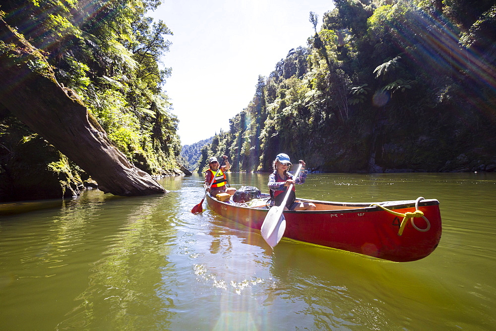 A girl and a woman on a canoe trip on the Whanganui River, North Island, New Zealand