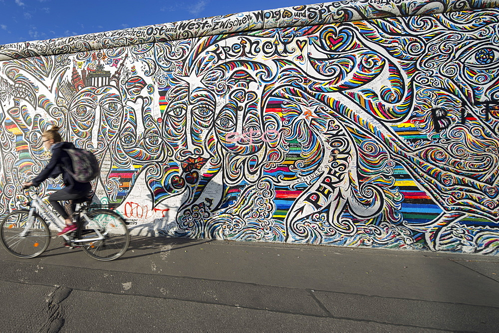Woman riding her bicycle past the Berlin Wall, East Side Gallery, Friedrichshain, Berlin, Germany