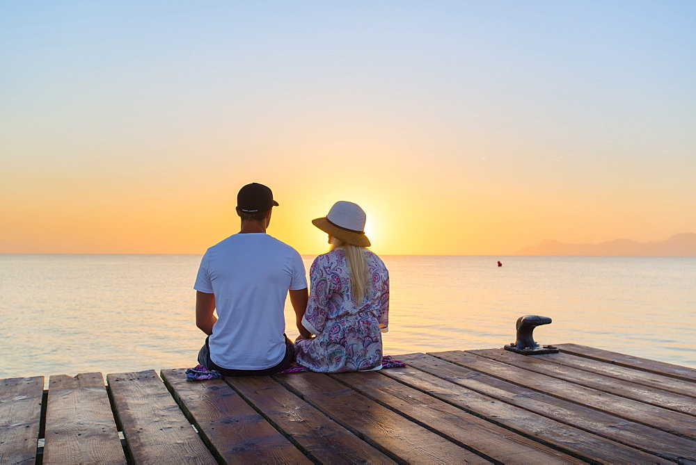 Young couple sitting at the end of a jetty in the morning atmosphere and enjoying the view of the sunrise. Playa de Muro beach, Alcudia, Mallorca, Balearic Islands, Spain - 1113-102280