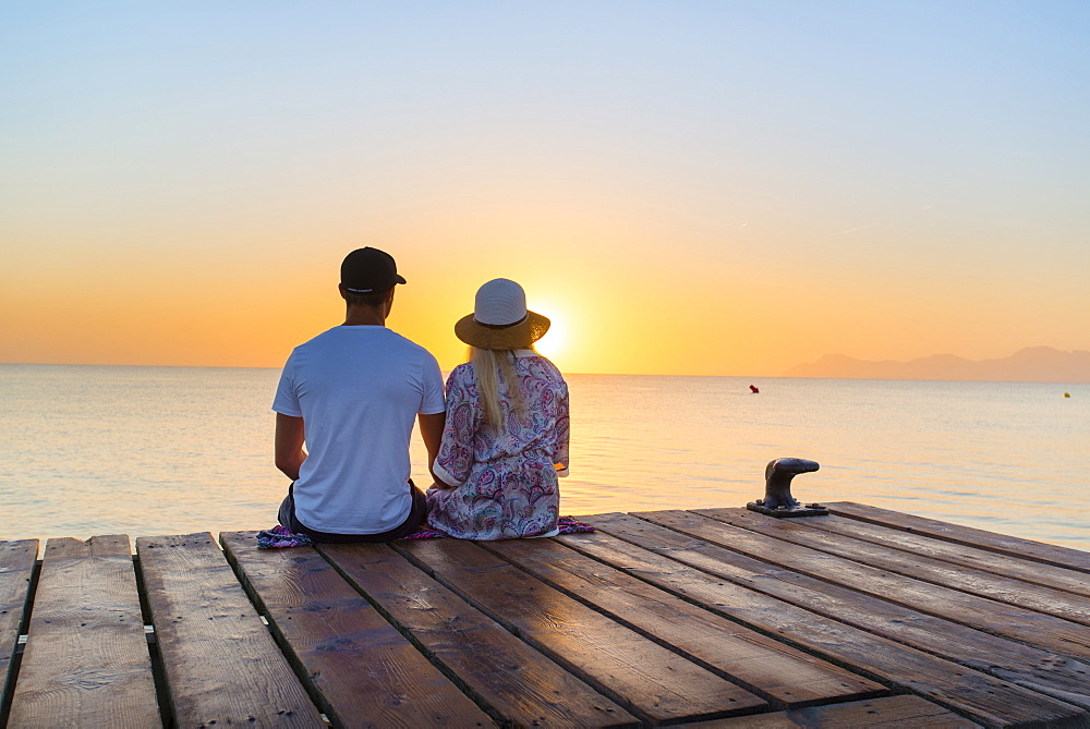Young couple sitting at the end of a jetty in the morning atmosphere and enjoying the view of the sunrise. Playa de Muro beach, Alcudia, Mallorca, Balearic Islands, Spain
