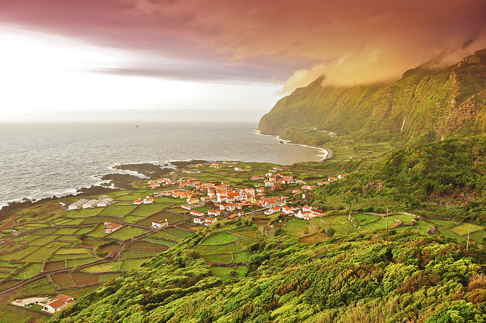 sunset and dramatic clouds over Faja Grande with terraces fields, white houses and steep coast, Island of Monchique in the sea, westermost point of Europe, view from the old whale outlook, Island of Flores, Azores, Portugal, Europe, Atlantic Ocean