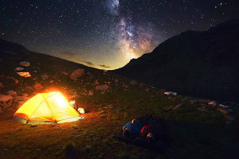 Two hikers watch the starry sky and milky way, camping spot in the Pfunderer Mountains, South Tyrol, Italy - 1113-102406