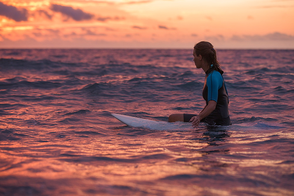 Young female surfer sitting on her surfboard in the water and waiting for a wave at sunset, Sao Tome, Sao Tome and Principe, Africa