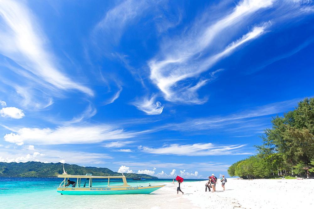 Tourists near a boat at white sandy beach, Gili Meno, Lombok, Indonesia