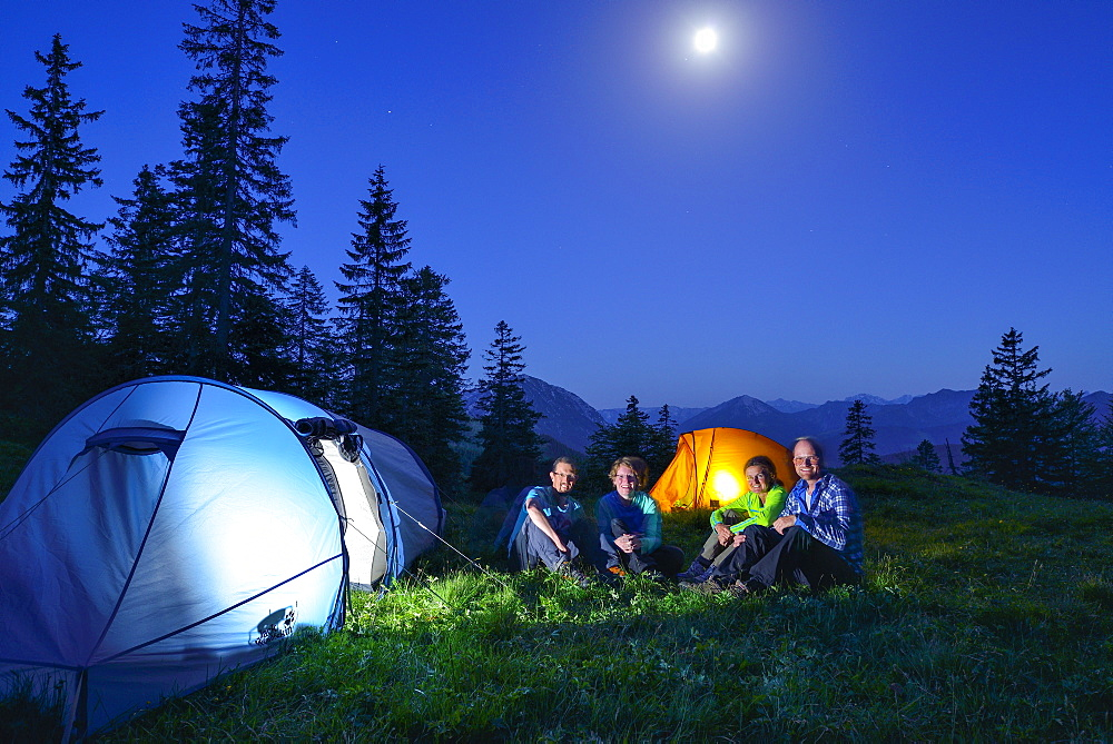 Four persons sitting in front of two illuminated tents, Blauberge, Bavarian Prealps, Upper Bavaria, Bavaria, Germany