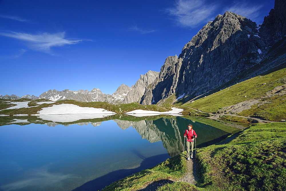 Woman hiking along lake Steinsee, Steinkarspitze and Schneekarlespitze in background, Lechtal Alps, Tyrol, Austria