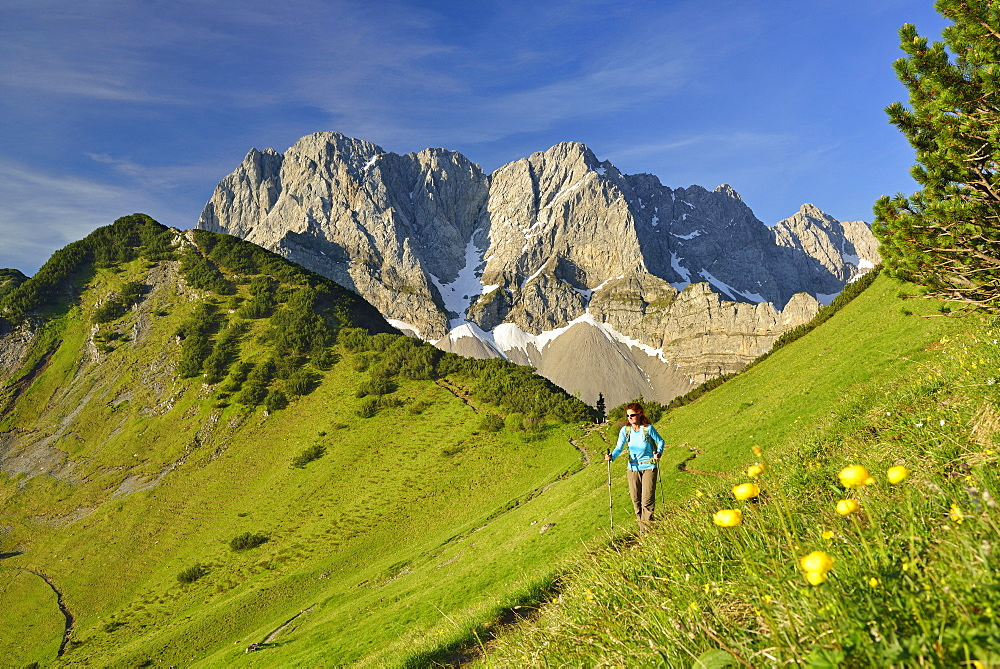 Woman hiking along trail, Lamsenspitze, Schafkarspitze and Hochglueck in background, Karwendel, Tyrol, Austria