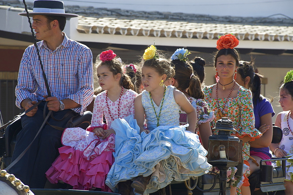 Girls and young woman in q horse carriage in Flamenco dresses, Pilgrims in front of the church at El Rocio at Pentecost, Huelva, Andalusien, Spanien