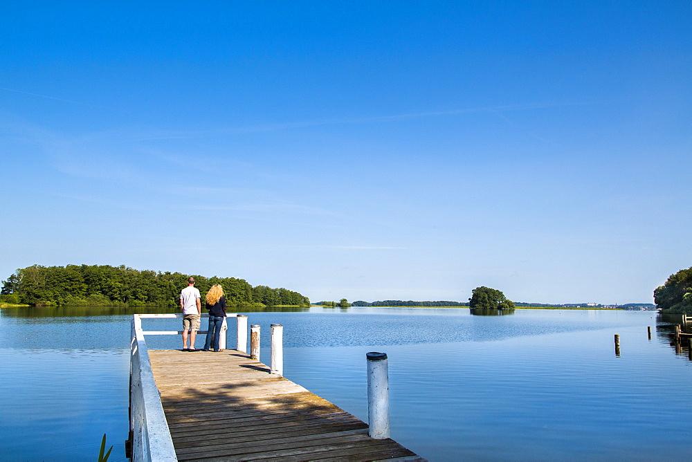 Couple on a pier at lake Ploen, Bosau, Holstein Switzerland, Ostholstein, Schleswig-Holstein, Germany