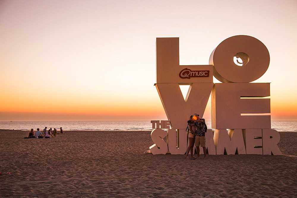 Couple taking a selfie photograph with smartphone in front of Love sculpture on the beach at sunset, Ostend, Flanders, Flemish Region, Belgium - 1113-102627