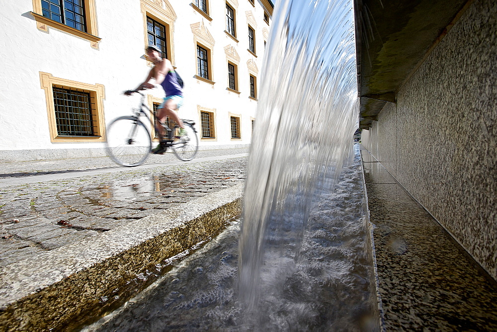 Young female cyclist riding past a fountain, Kempten, Bavaria, Germany