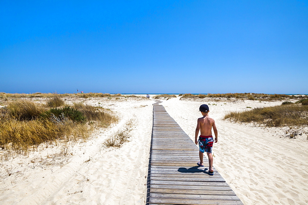 Boy on a boardwalk, walking to the beach, Armona island, Olhao, Algarve, Portugal