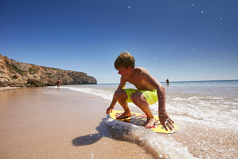 Young skimboarder on Zavial beach, West Coast, Algarve, Portugal