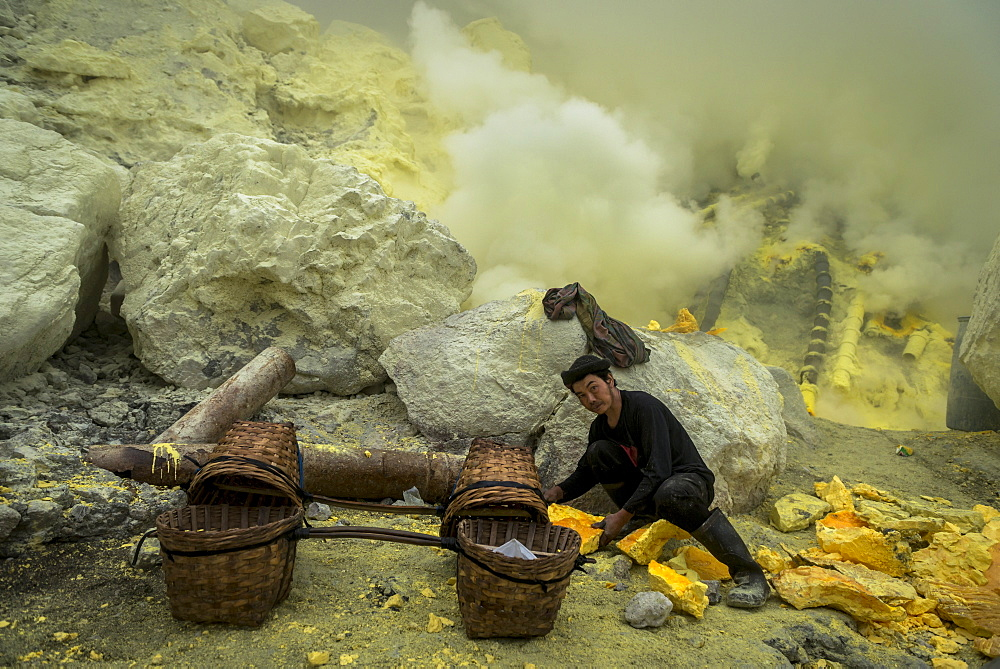 Miners of the devil mine of Ijen volcano loading transport baskets with sulfur - Indonesia, Java - 1113-102708