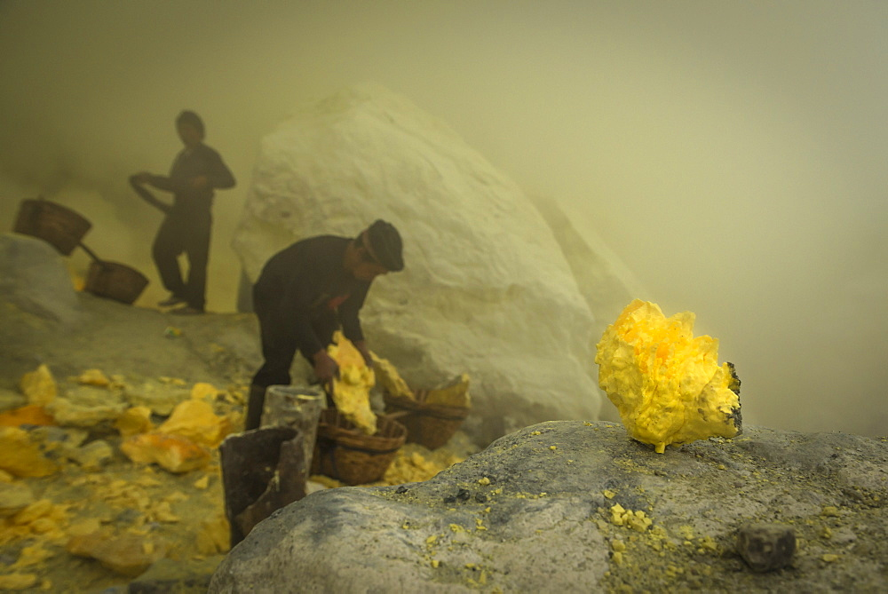 Miners of the devil mine of Ijen volcano loading transport baskets with sulfur - Indonesia, Java