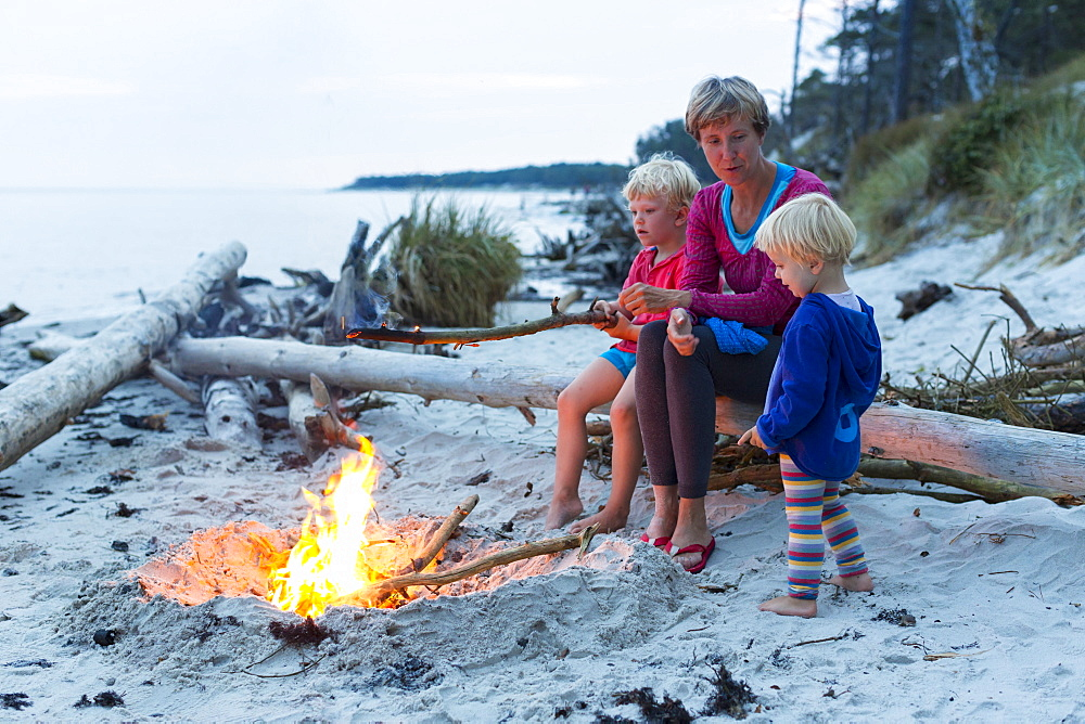 Familiy, mother and two children sitting around a campfire, adventure, dream beach between Strandmarken und Dueodde, sandy beach, summer, Baltic sea, Bornholm, Strandmarken, Denmark, Europe, MR