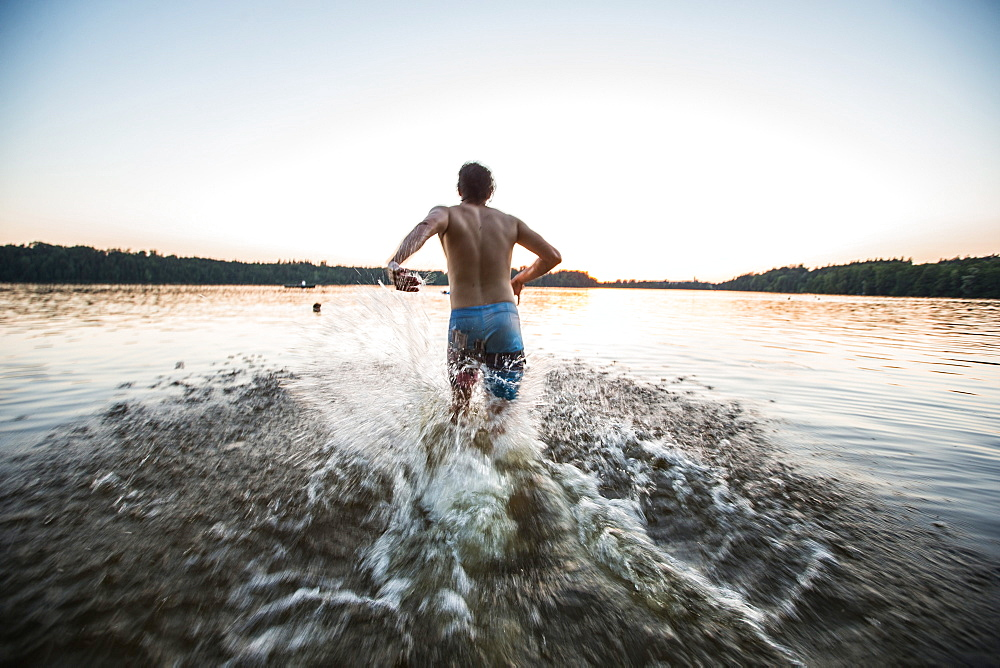 Young man running into the water of a lake, Freilassing, Bavaria, Germany - 1113-102739