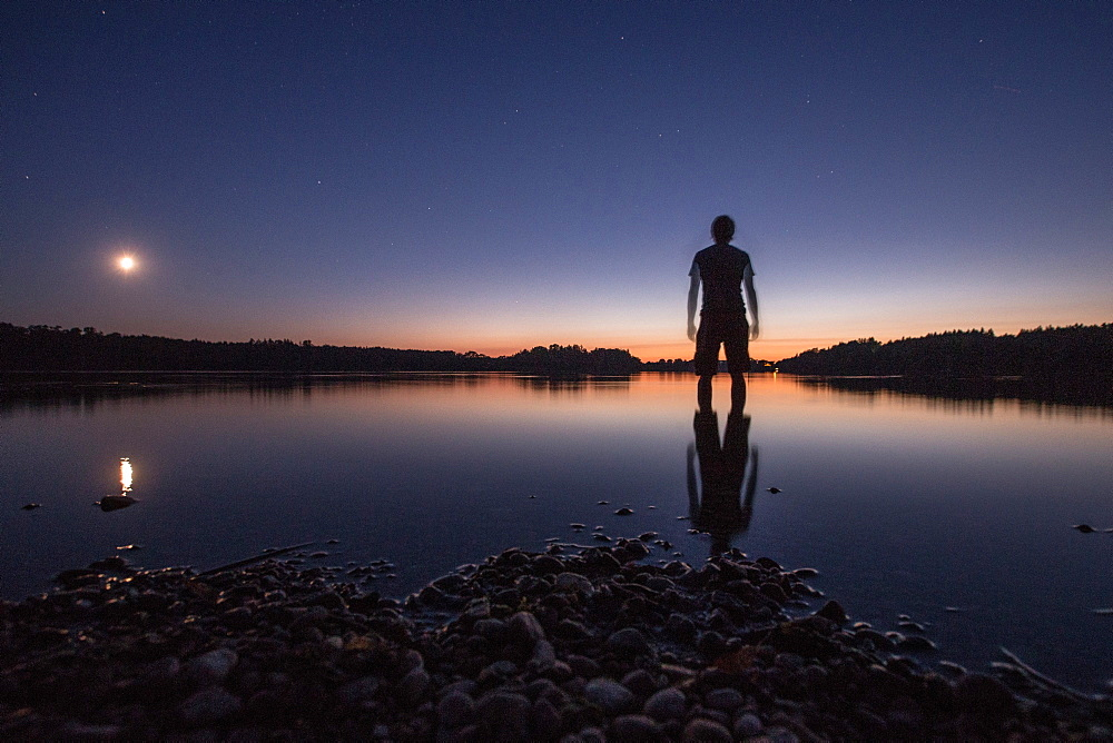 Young man standing in a lake at night, Freilassing, Bavaria, Germany