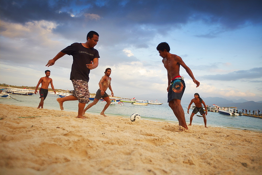 Young locals playing football on Trawangan beach, Gili Trawangan, Lombok, Indonesia