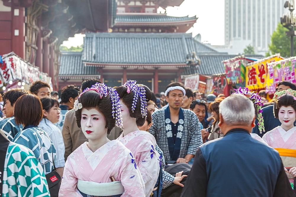 Three Geisha and man in yukata with stroller during Sanja Matsuri, Asakusa, Tokyo, Japan