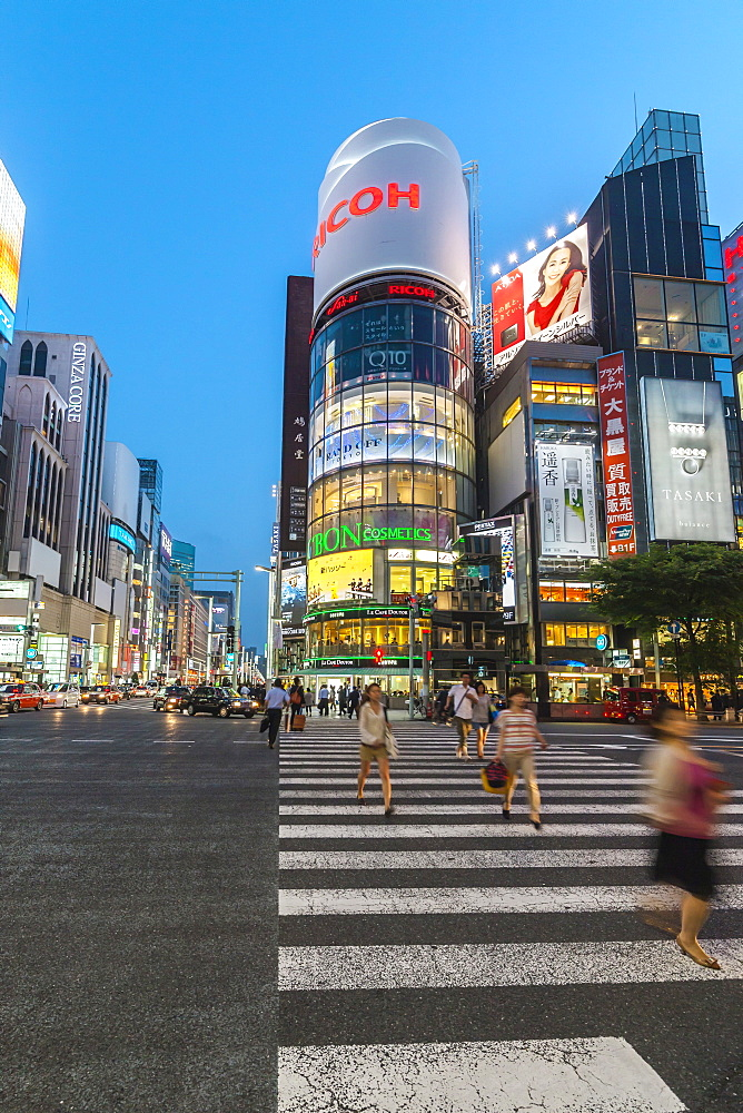 Zebra Crossing with moving women at Ricoh Imaging Square in Ginza during blue hour, Chuo-ku, Tokyo, Japan