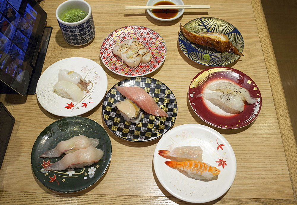 Selection of plates with Nigiri sushi at Kaiten sushi restaurant, Shibuya, Tokyo, Japan