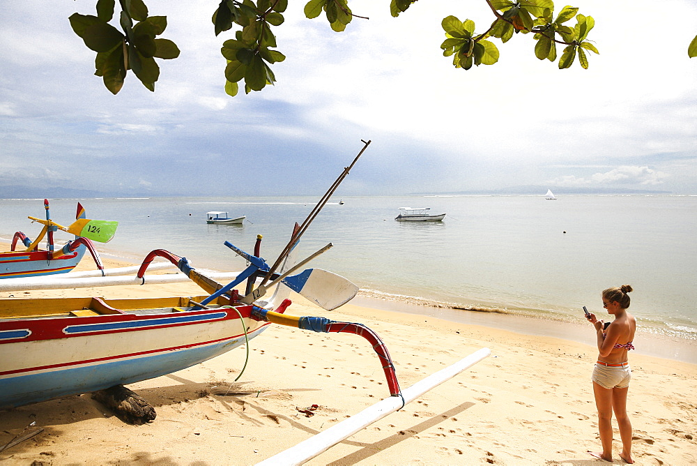 Woman taking pictures of a colorful traditional fishing boat at beach, Sanur, Denpasar, Bali, Indonesia