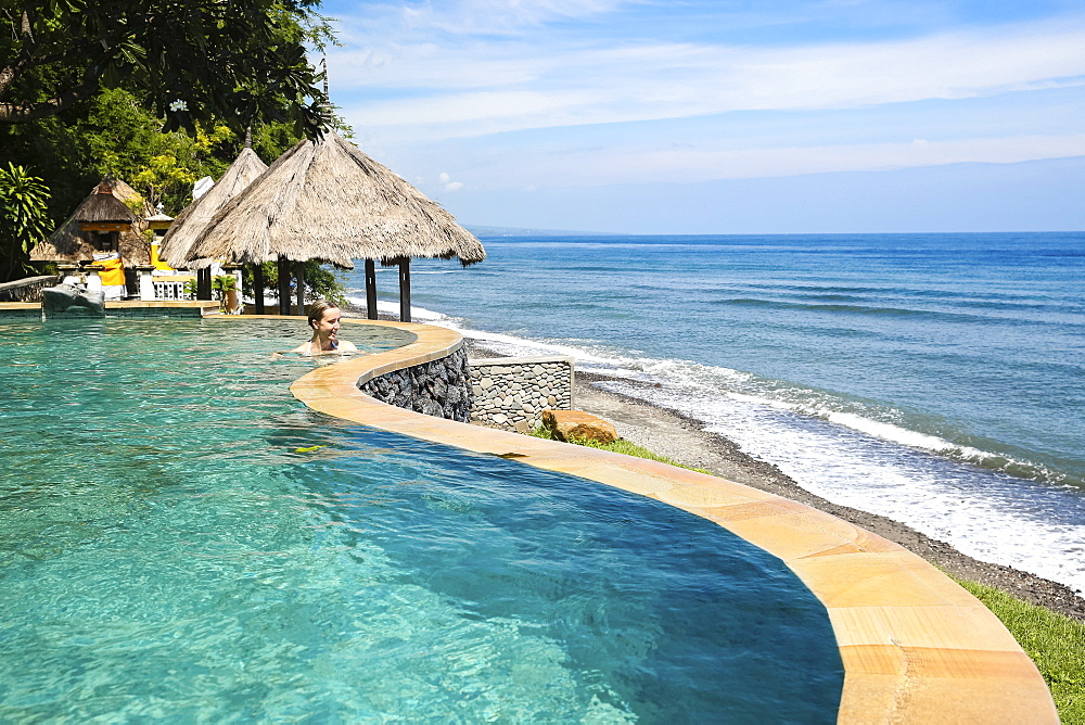 Woman in an infinity pool of a hotel with view to Indian Ocean, Amed, Bali, Indonesia