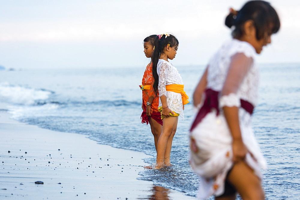 Girls standing in shallow water, Odalan, Pura Goa Lawah, Padangbai, Bali, Indonesia