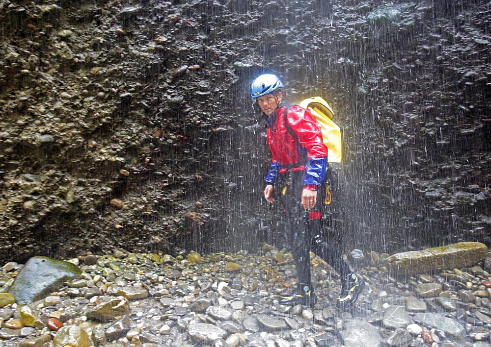 Man walking throuhg gorge, swim and hike canyon Raebloch, Emmental valley, Canton of Bern, Switzerland, MR - 1113-103724