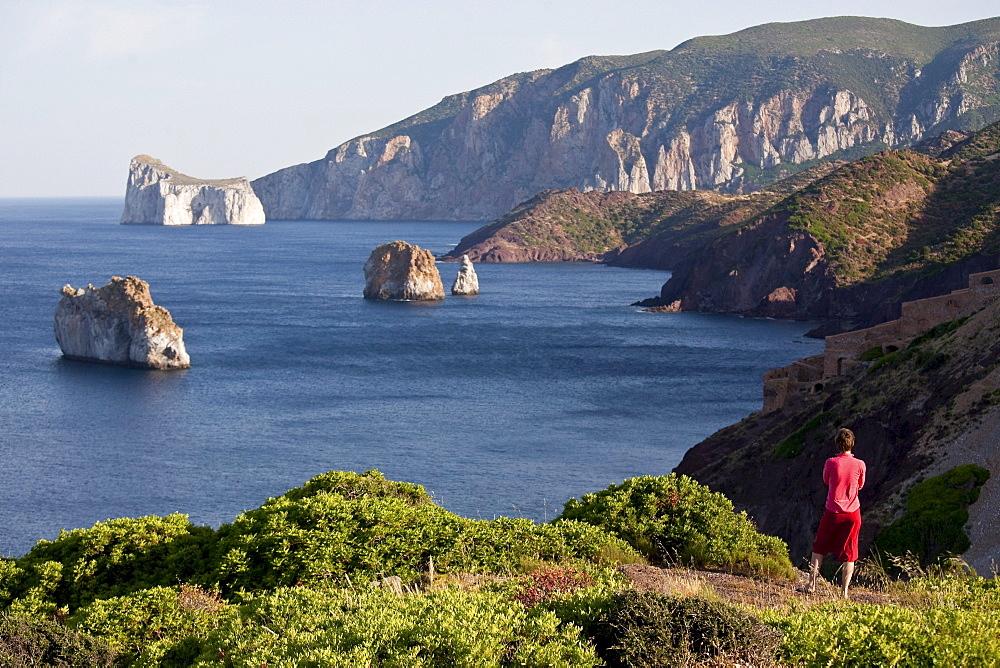Pan di Zucchero, woman looking at rock off shore, Masua, Sardinia, Italy, Europe