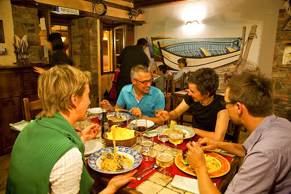 People sitting laughing at a table at a fish restaurant, Posada, Sardinia, Italy, Europe