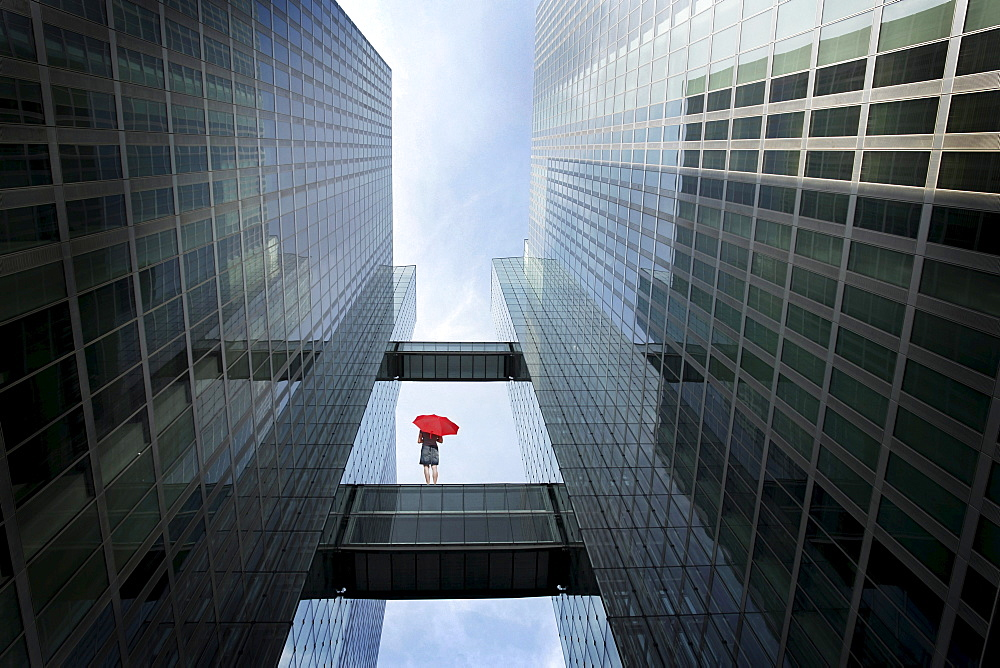 Woman with red umbrella between high-rise buildings, Munich, Bavaria, Germany (digital composite)