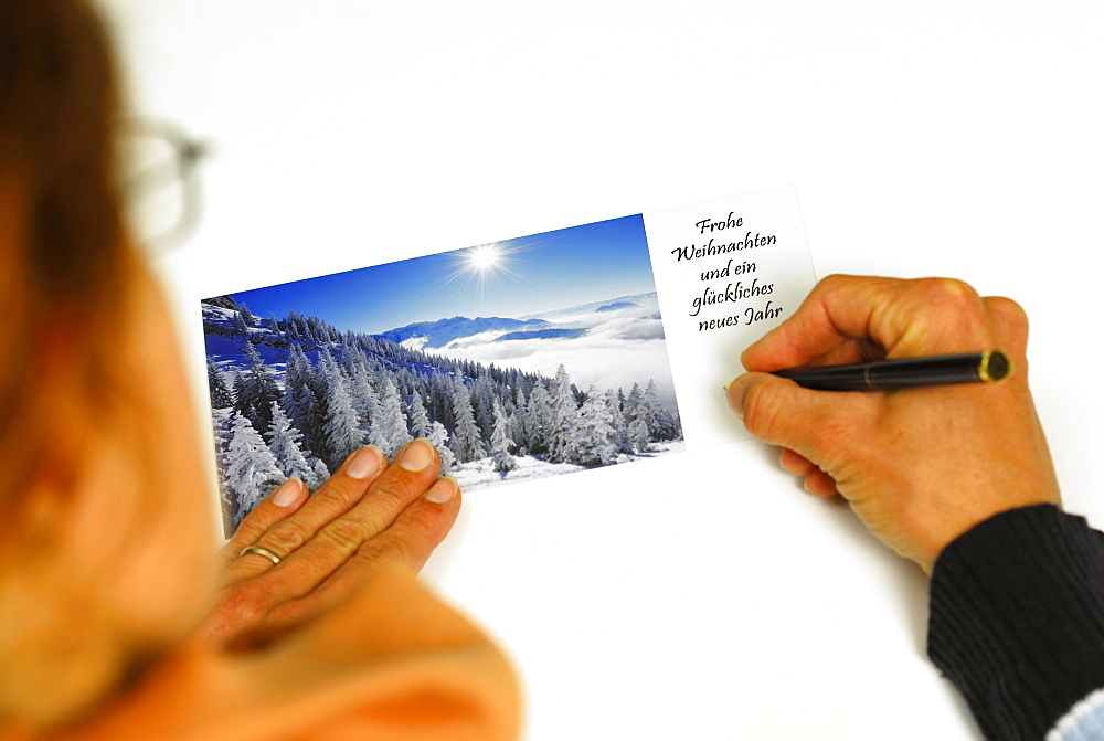 Woman writing Christmas card with winter subject