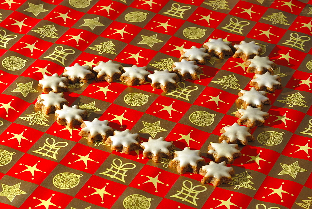 Christmas cookies cinnamon stars laying in heart shape on wrapping paper