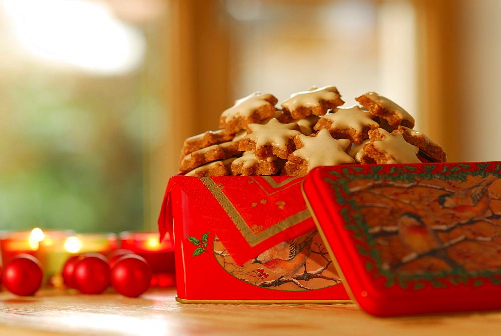 Christmas cookies cinnamon stars piling up in Christmas tin