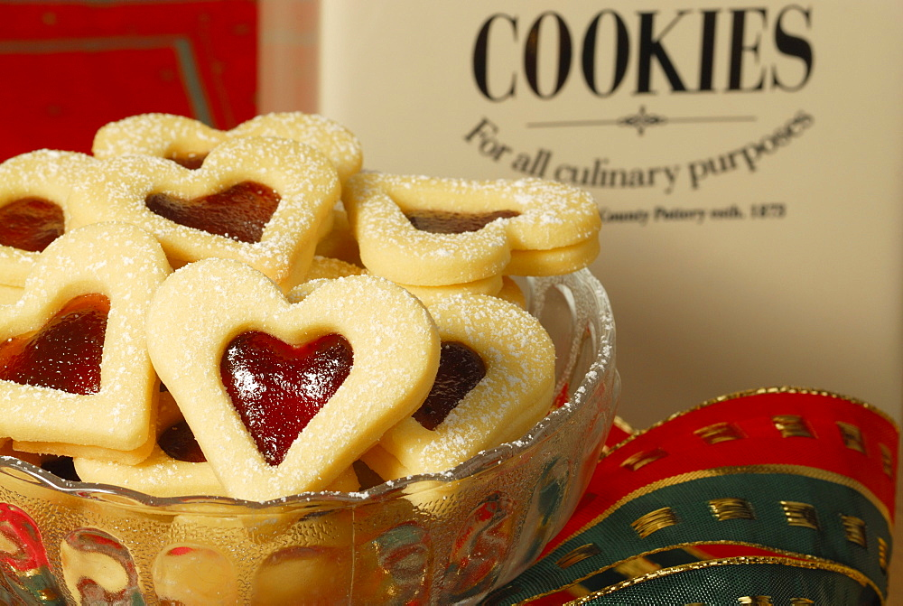 Christmas cookies raspberry hearts covered with sugar piling up in glasbowl, Christmas decoration in background