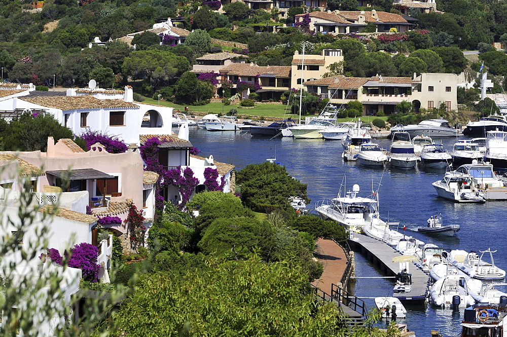 View at houses on the waterfront and boats at a jetty, Porto Cervo, Costa Smeralda, North Sardinia, Italy, Europe