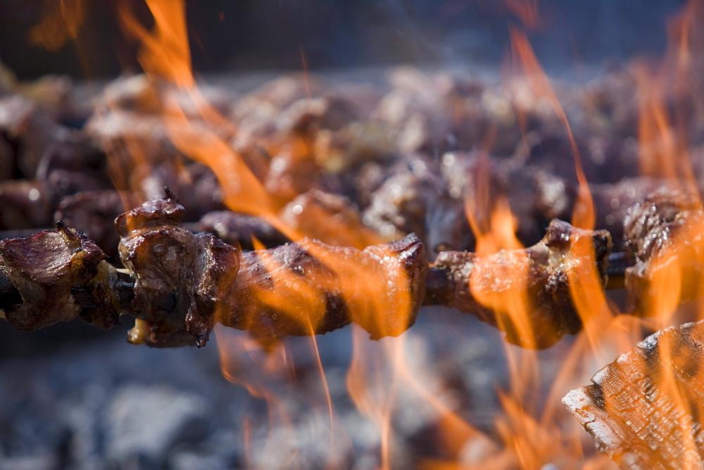 Grilling Espetada beef skewer kebabs over an open fire at a religiois festival, Ponta Delgada, Madeira, Portugal