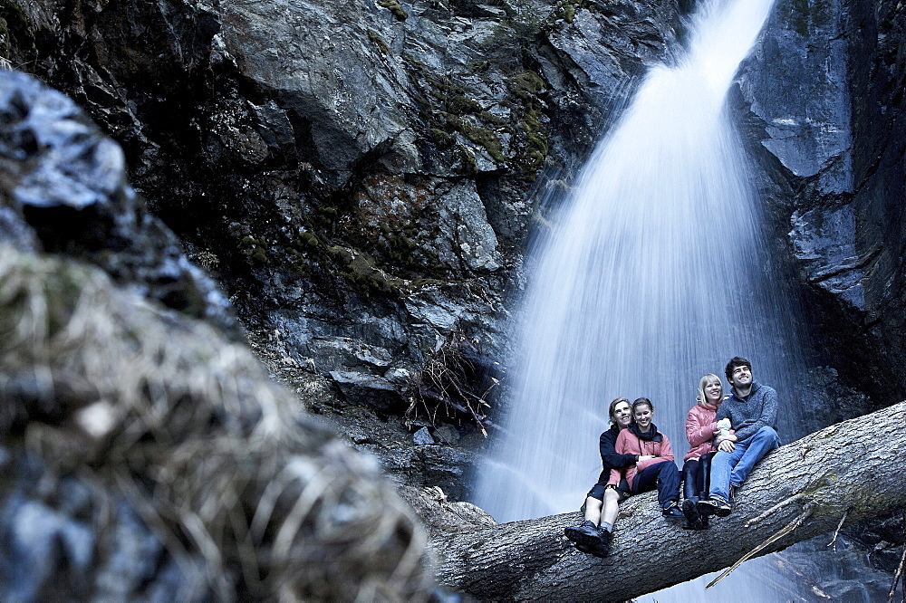 Two couples sitting on a trunk in front of a waterfall, See, Tyrol, Austria