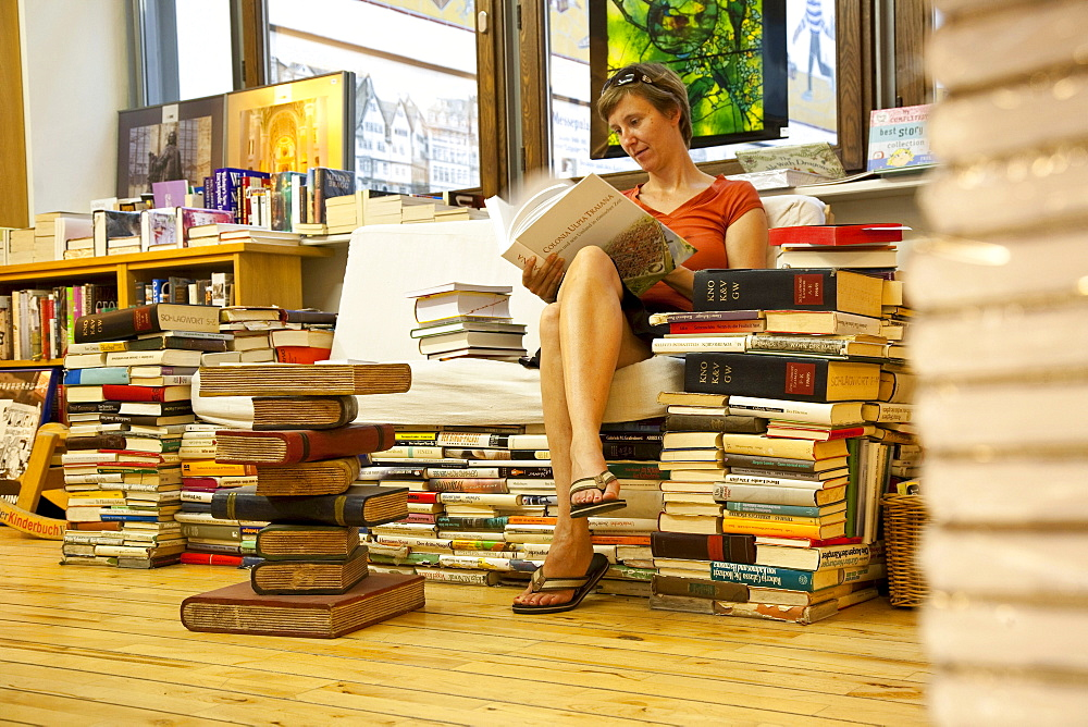 Woman sitting in a bookshop, Leipzig, Saxony, Germany