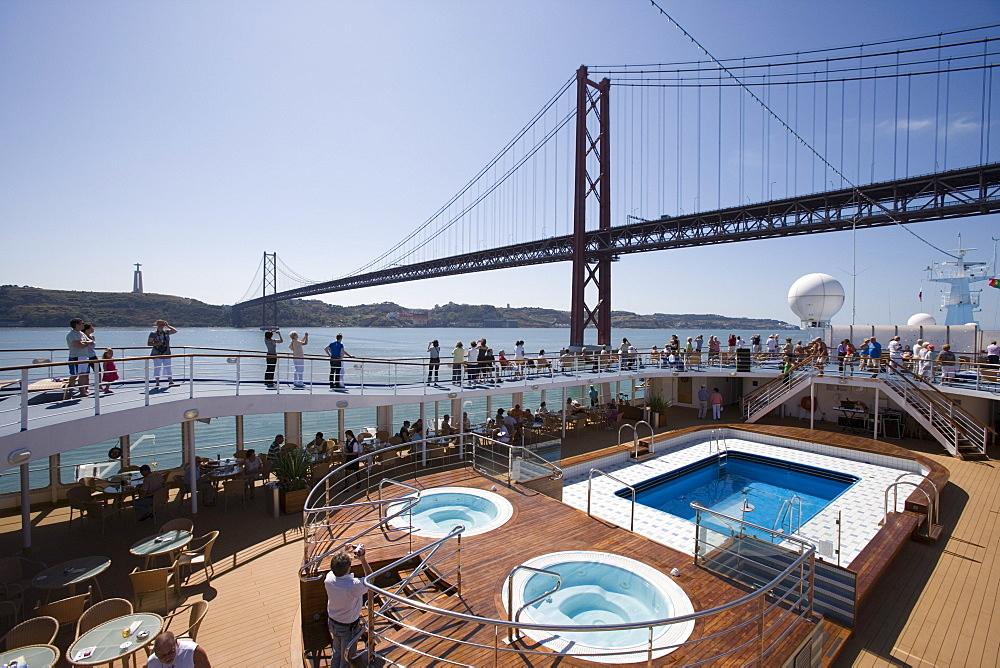 Pool deck of cruiseship MS Delphin Voyager as vessel approaches Ponte 25 de Abril Bridge on Tagus River, Lisbon, Lisboa, Portugal