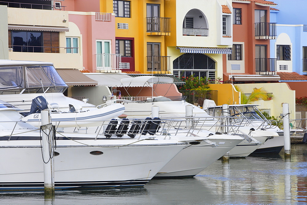 Boats are moored at Palmas del Mar harbour in front of colourful houses, Palmas del Mar, Puerto Rico, America