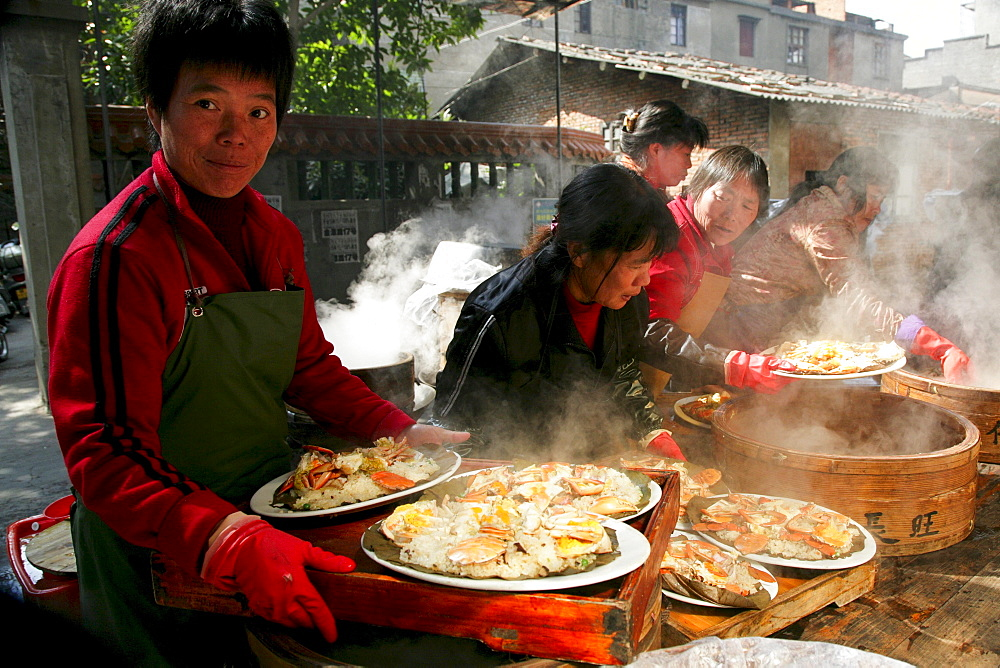 Waitress with steaming plates of sea food, steaming in bamboo baskets, Chinese cuisine, Jinfeng, Changle, Fujian province, China, Asia
