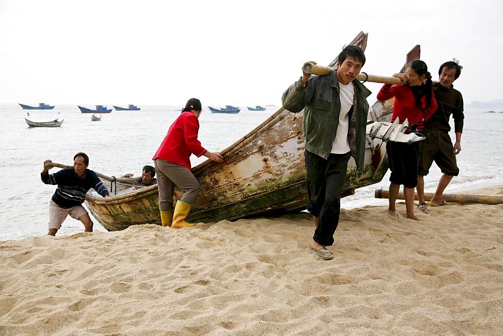 Fishermen pulling a boat out of the water, Mazu island, Meizhou Island, Fujian province, China, Asia