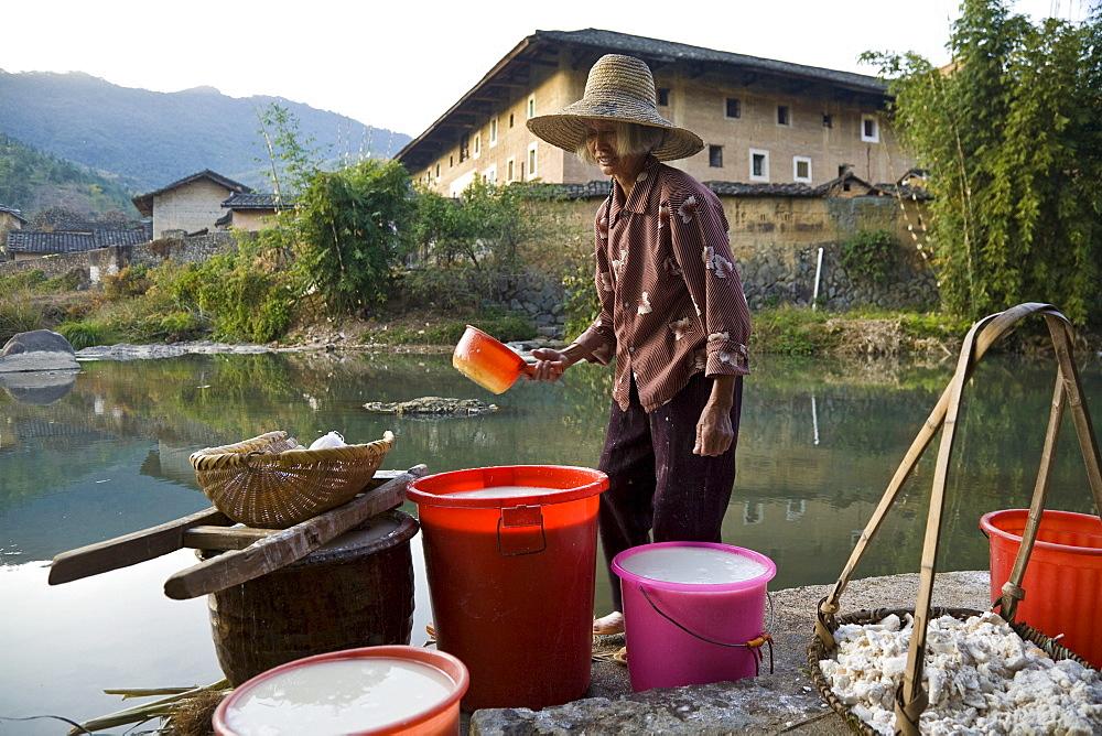 Chinese farmer fetching water from a small stream, village of the Hakka, Hongkeng, Longyan, Fujian, China, Asia