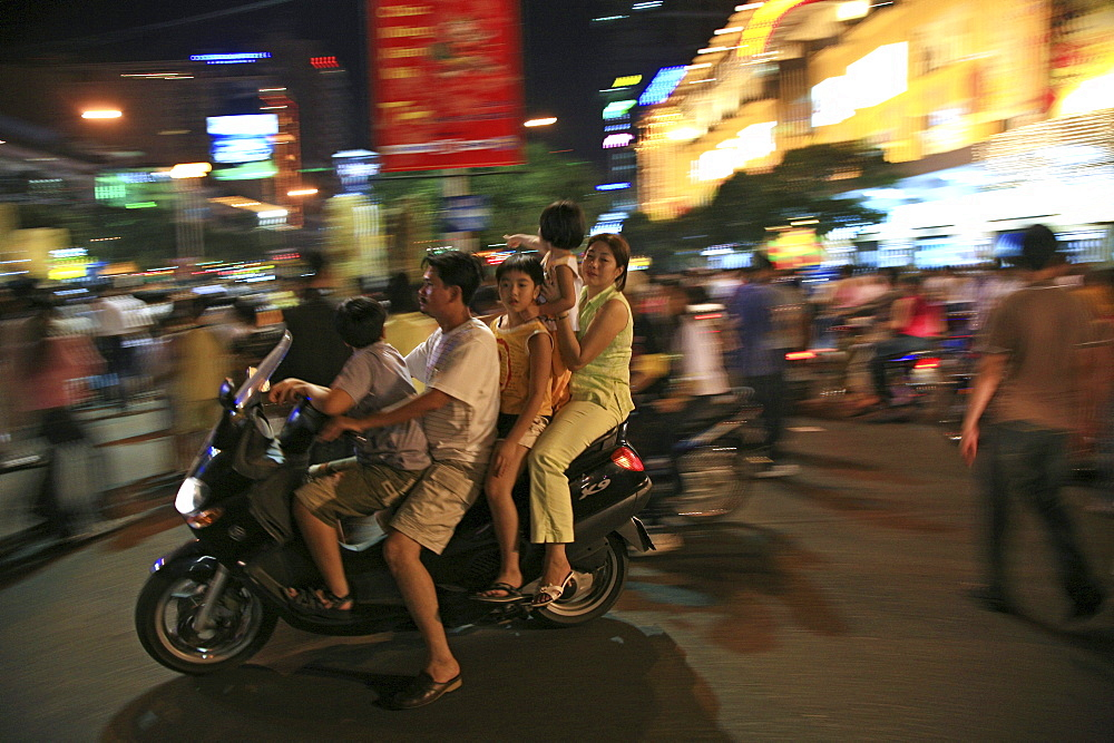 Family with children driving a scooter during the Tet festival at night, Saigon Ho Chi Minh City, Vietnam, Asia