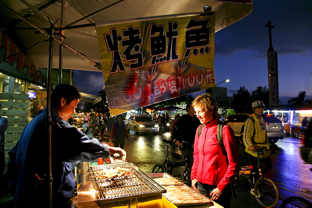 Tourist buying grilled octopus at the night market, Kenting National Park, Kenting, Kending, Republic of China, Taiwan, Asia