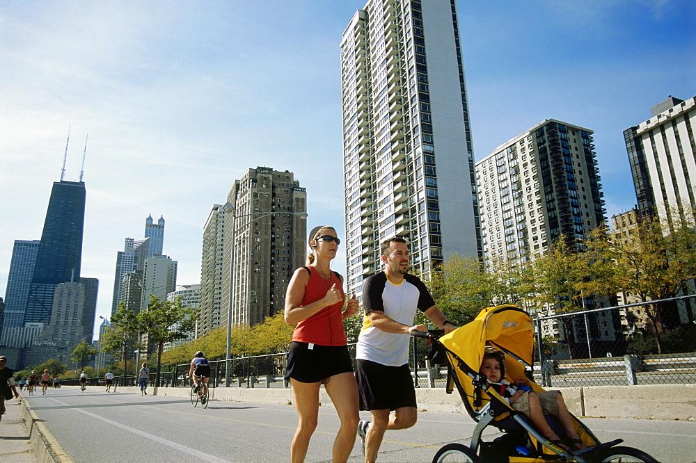 Young family jogging atOak Street Beach, Gold Coast, Chicago, Illinois, USA
