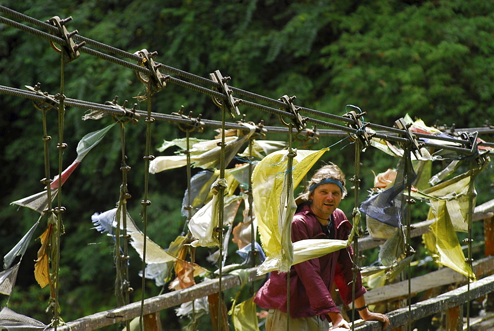 Man on suspension bridge with prayer flags, Trek towards Gocha La in Kangchenjunga region, Sikkim, Himalaya, Northern India, Asia
